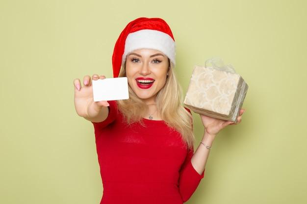 Widok z przodu ładna kobieta trzyma prezent i karta bankowa na kolorach zielonych ścian boże narodzenie śnieg nowy rok wakacje emocje