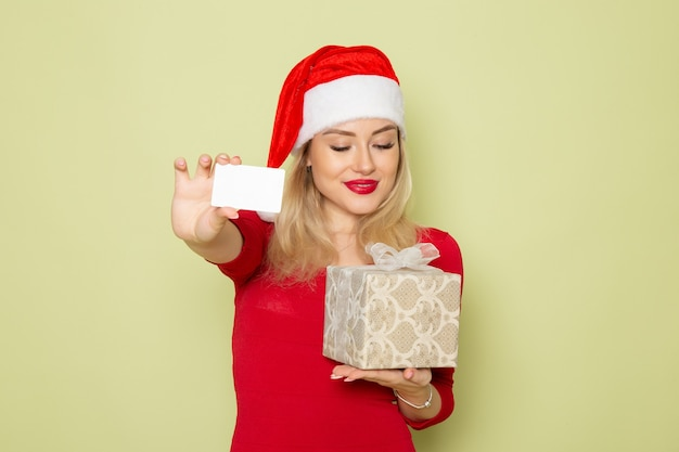 Widok z przodu ładna kobieta trzyma prezent i kartę bankową na zielonej ścianie wakacje boże narodzenie