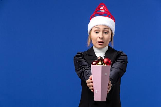 Widok z przodu ładna kobieta trzyma zabawki choinkowe na niebieskiej ścianie niebieski wakacje nowy rok