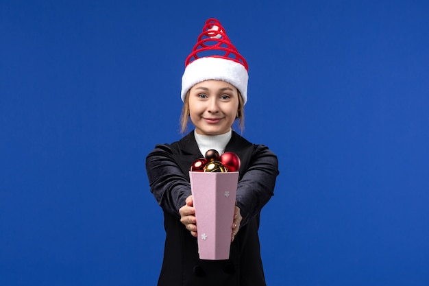 Widok z przodu ładna kobieta trzyma zabawki choinkowe na niebieskiej ścianie niebieskie wakacje nowy rok