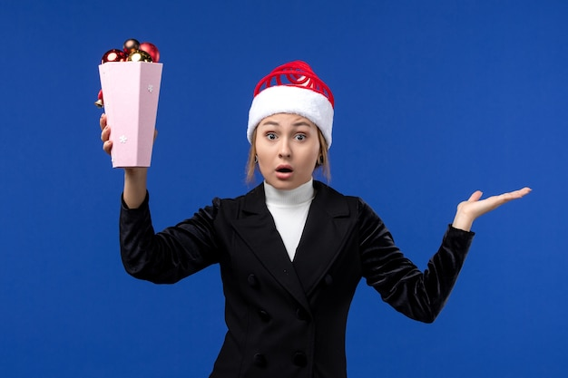 Widok z przodu ładna kobieta trzyma zabawki drzewka na niebieskiej ścianie kobieta wakacje nowy rok niebieski