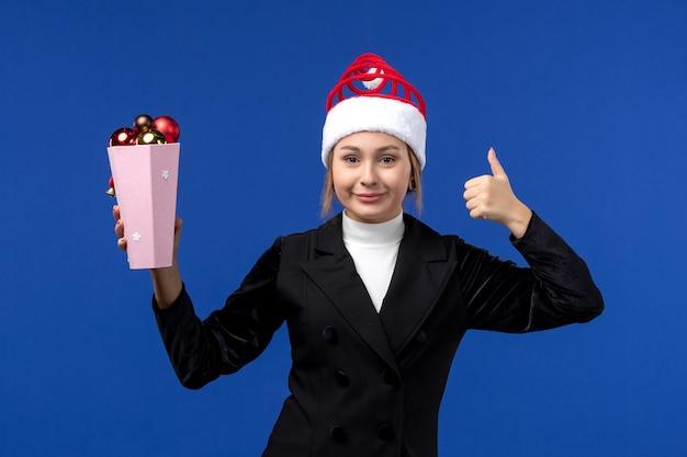 Widok z przodu ładna kobieta trzyma zabawki drzewka na niebieskiej ścianie nowy rok kobieta niebieski wakacje