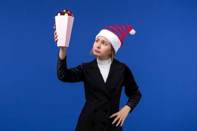 Widok z przodu ładna kobieta trzyma zabawki drzewka na niebieskim biurku kobieta niebieski wakacje nowy rok