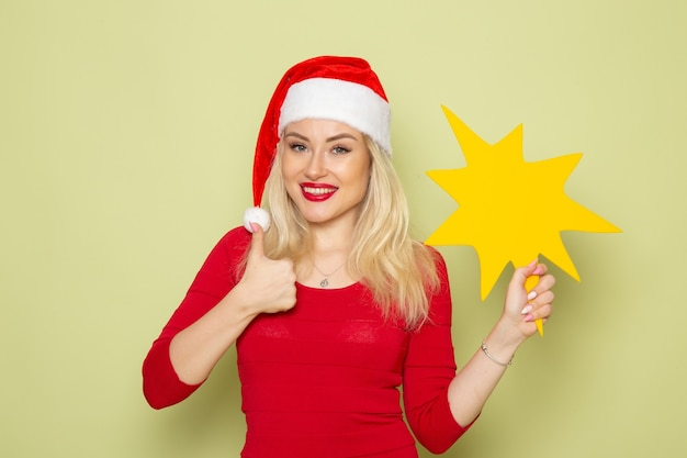 Widok z przodu ładna kobieta trzymająca dużą żółtą postać na zielonej ścianie kolor wakacje emocje śnieg nowy rok boże narodzenie