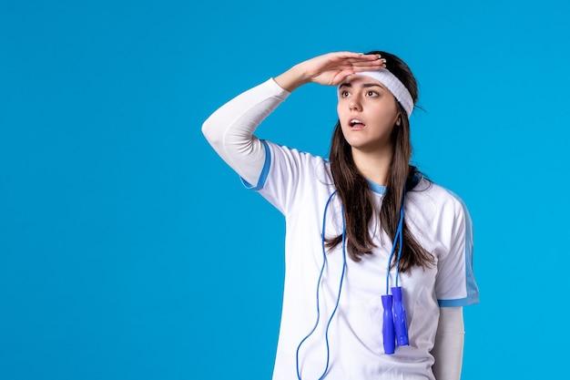 Widok z przodu ładna kobieta w ubraniach sportowych z skakanka na niebiesko
