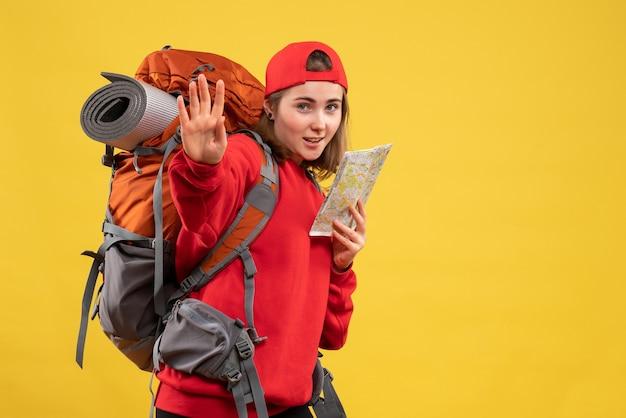 Widok z przodu ładna podróżniczka z plecakiem trzymając mapę macha ręką