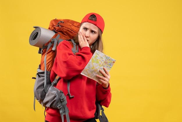 Widok z przodu ładna podróżniczka z plecakiem trzymając mapę, zastanawiając się