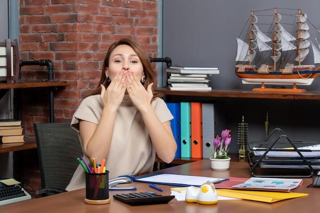 Widok z przodu ładnej kobiety dmuchającej buziaka pracującej w biurze