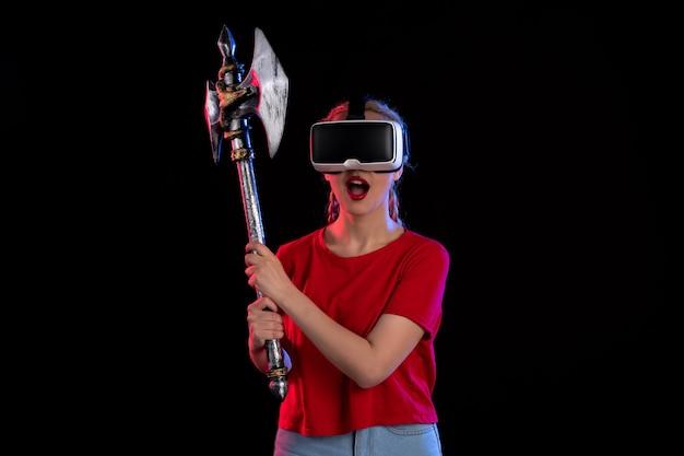 Widok z przodu ładnej kobiety grającej w vr z ciemnym toporem bojowym