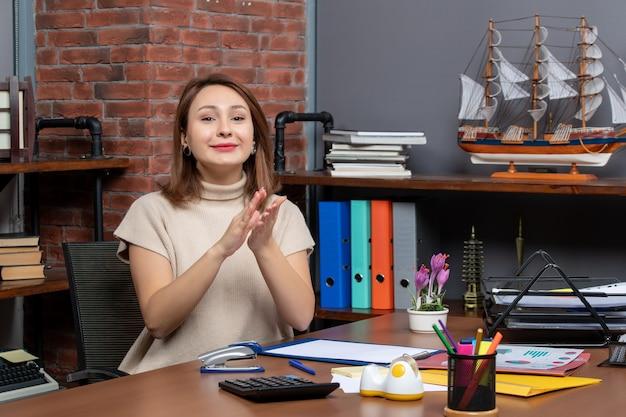 Widok z przodu ładnej kobiety klaszczącej w dłonie pracującej w biurze