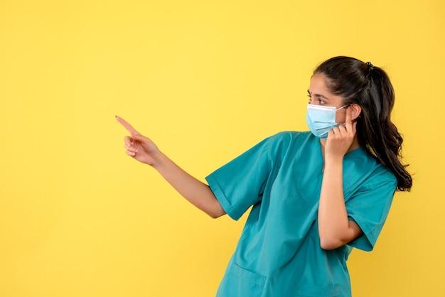 Widok z przodu ładnej kobiety lekarza z maską medyczną, wskazując w lewo na żółtej ścianie