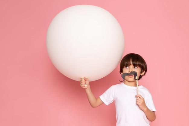 Widok z przodu ładny chłopiec dziecko w białej koszulce trzyma białą piłkę na różowym biurku