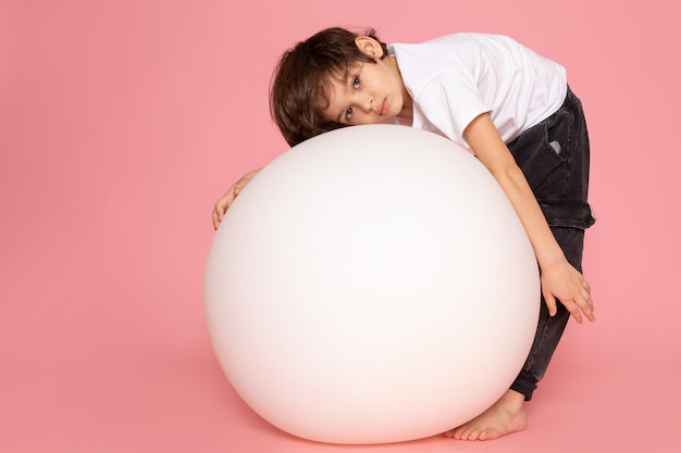 Widok z przodu ładny chłopiec w białej koszulce bawi się białą okrągłą piłką na różowej podłodze