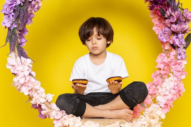 Widok z przodu ładny chłopiec w białej koszulce jedzący pączki choco na żółtym biurku