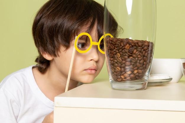 Widok z przodu ładny chłopiec w białej koszulce, patrząc na brązowe ziarna kawy na kamiennej podłodze