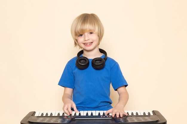 Widok z przodu ładny mały chłopiec uśmiecha się w niebieskiej koszulce z czarnymi słuchawkami, grając w małe słodkie pianino