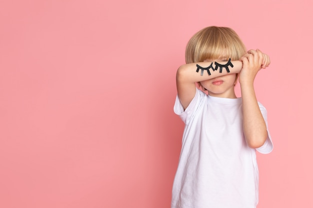 Widok z przodu ładny mały chłopiec w białej koszulce zamykającej oczy dłonią na różowej przestrzeni