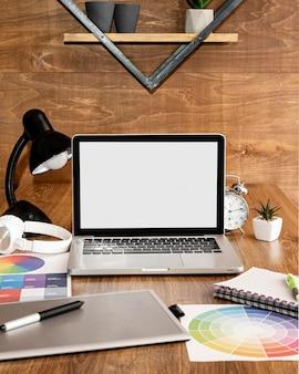 Widok z przodu laptopa na biurowym obszarze roboczym z lampą i notebookiem