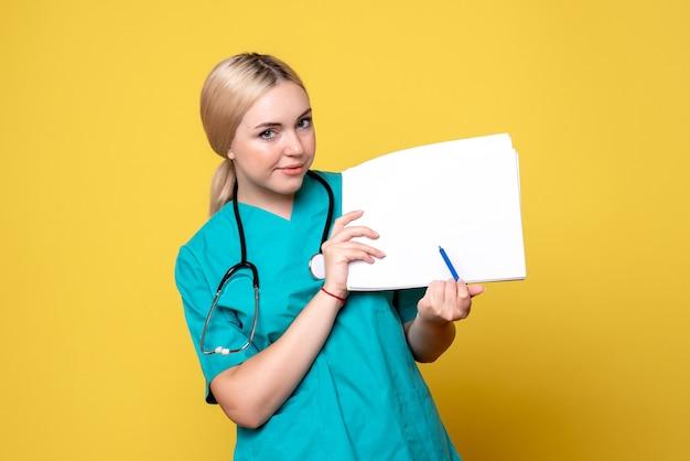 Widok z przodu lekarka trzymająca różne dokumenty, pielęgniarka szpitalna pandemii wirusa covid-19