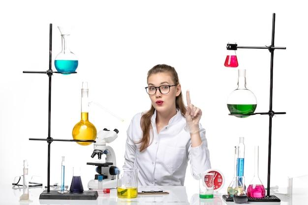 Widok z przodu lekarka w białym garniturze medycznym siedząca przed stołem z roztworami na jasnym białym tle wirus covid pandemiczny chemia
