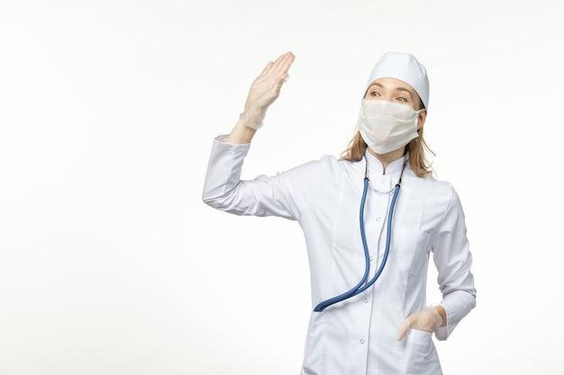Widok z przodu lekarka w białym kombinezonie medycznym i masce jako ochrona przed koronawirusem na białej podłodze choroba covid - choroba pandemiczna