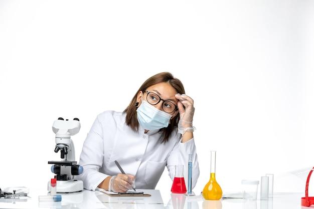 Widok z przodu lekarka w białym kombinezonie medycznym z maską z powodu covid pisania czegoś na jasnobiałej przestrzeni