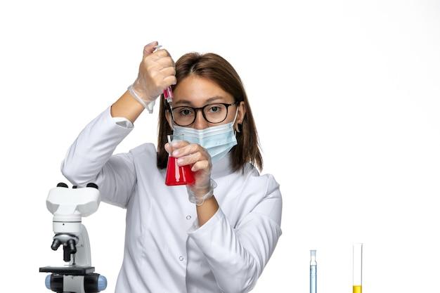 Widok z przodu lekarka w białym kombinezonie medycznym z maską z powodu covid pracy z roztworami na białej przestrzeni