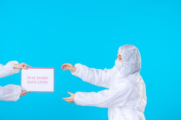 Widok z przodu lekarka w kombinezonie ochronnym i masce na niebieskim tle izolacja chorób wirusowych covid- nauka zdrowie pandemia medyczna