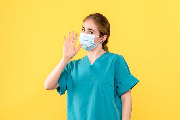Widok z przodu lekarka w masce macha na żółtym tle pandemiczny wirus choroby covid