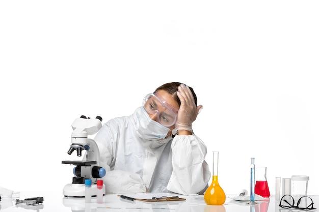 Widok z przodu lekarka w specjalnym garniturze i nosząca maskę czuje się zmęczona na białym tle covid - zdrowie wirusa koronawirusa pandemii