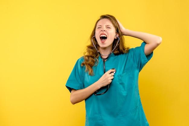 Widok z przodu lekarki krzyczącej na żółtej ścianie