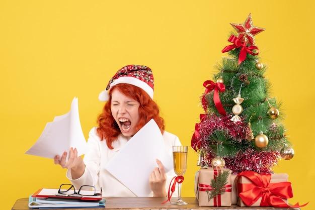 Widok z przodu lekarz kobiet posiadających dokumenty i siedzący z prezentami świątecznymi