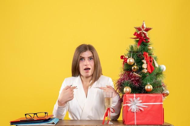 Widok z przodu lekarz kobieta siedzi przed stołem z prezentami święta i drzewa na żółtym tle