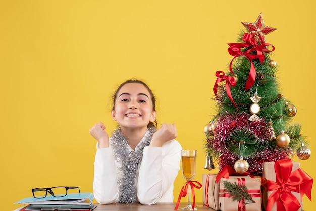 Widok z przodu lekarz kobieta siedzi wokół prezentów świątecznych i drzewa na żółtym tle