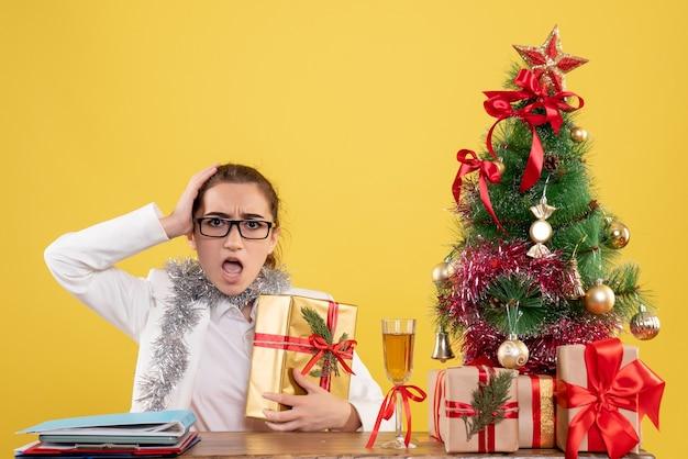 Widok z przodu lekarz kobieta siedzi wokół prezentów świątecznych i prezent gospodarstwa drzewo na żółtym tle