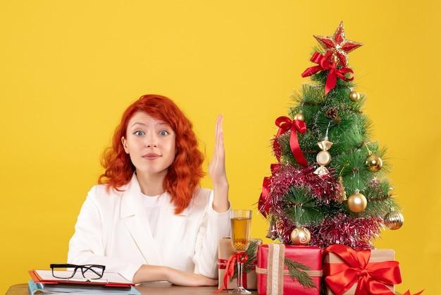 Widok z przodu lekarz kobieta siedzi za stołem z prezentami świątecznymi na żółtym tle