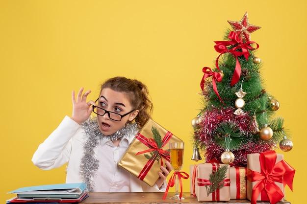 Widok z przodu lekarz kobieta siedzi za stołem z prezentami xmas i drzewo na żółtym tle
