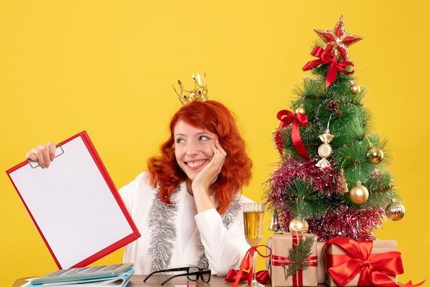 Widok z przodu lekarz kobieta trzyma notatkę wokół drzewa xmas i prezenty