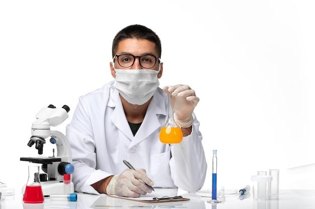 Widok z przodu lekarz mężczyzna w białym garniturze medycznym iz maską pracujący z roztworami na białym biurku