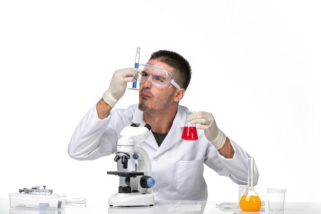 Widok z przodu lekarz mężczyzna w białym garniturze medycznym pracujący z roztworami na jasnych białych przestrzeniach