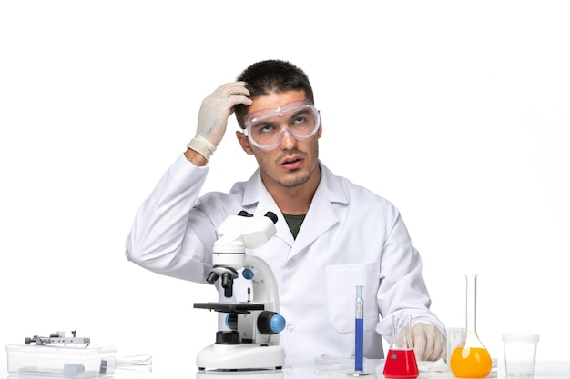 Widok z przodu lekarz mężczyzna w białym garniturze medycznym siedzi z roztworami i myśli na białej przestrzeni