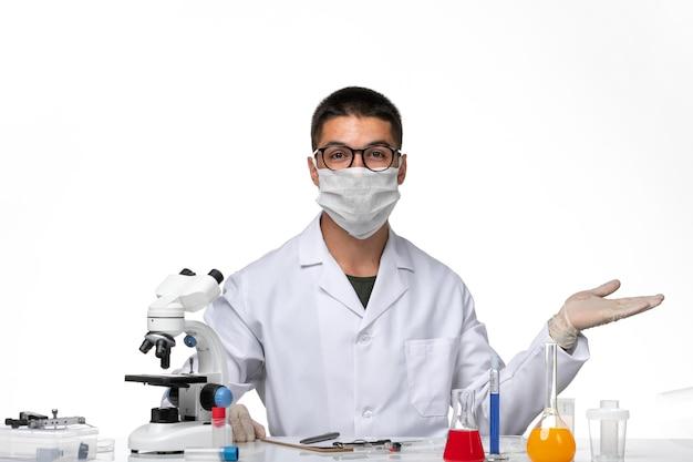 Widok z przodu lekarz mężczyzna w białym garniturze medycznym z maską z powodu covid na białym biurku