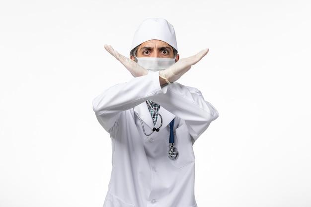 Widok z przodu lekarz mężczyzna w białym kombinezonie medycznym z maską z powodu covid krzyżujących ręce na białej powierzchni