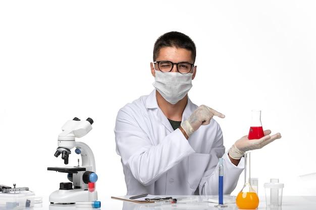 Widok z przodu lekarz mężczyzna w białym kombinezonie medycznym z maską z powodu covid na białej przestrzeni