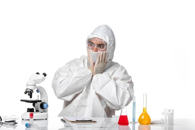 Widok z przodu lekarz mężczyzna w kombinezonie ochronnym z maską z powodu covid z zaskoczonym wyrazem na białym biurku