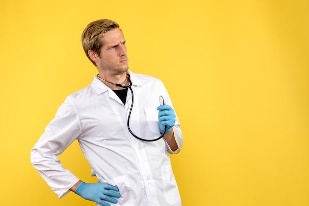 Widok z przodu lekarz mężczyzna zdezorientowany na żółtym tle medyk wirusa zdrowia emocji