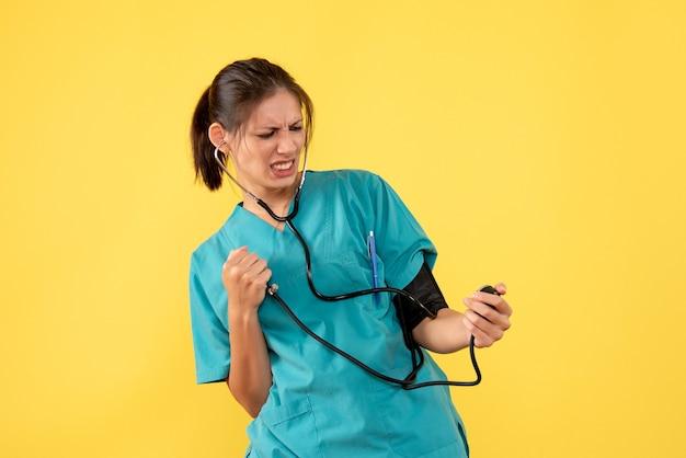 Widok Z Przodu Lekarz W Koszuli Medycznej Sprawdzanie Jej Ciśnienia Na żółtym Tle Darmowe Zdjęcia