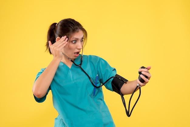 Widok z przodu lekarz w koszuli medycznej sprawdzanie jej ciśnienia na żółtym tle