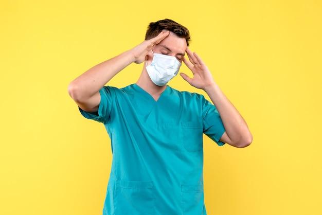 Widok z przodu lekarza męskiego cierpiącego na ból głowy na żółtej ścianie