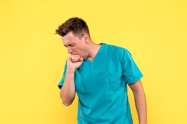 Widok z przodu lekarza męskiego gryzącego rękę od nerwu na żółtej ścianie